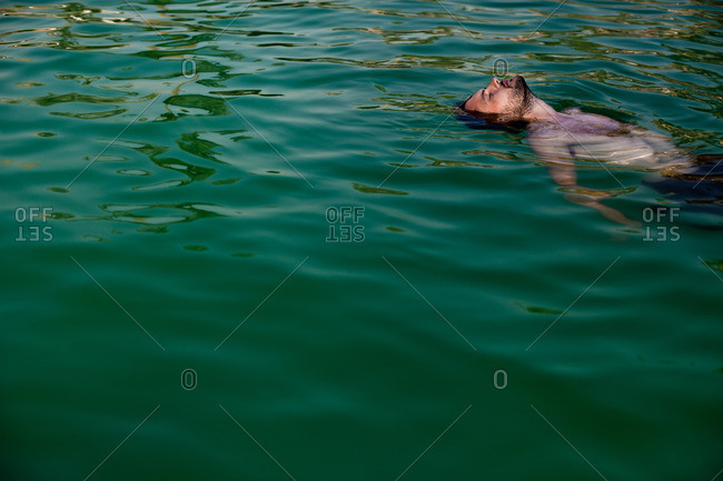 August 8, 2014: Man floating on his back in water