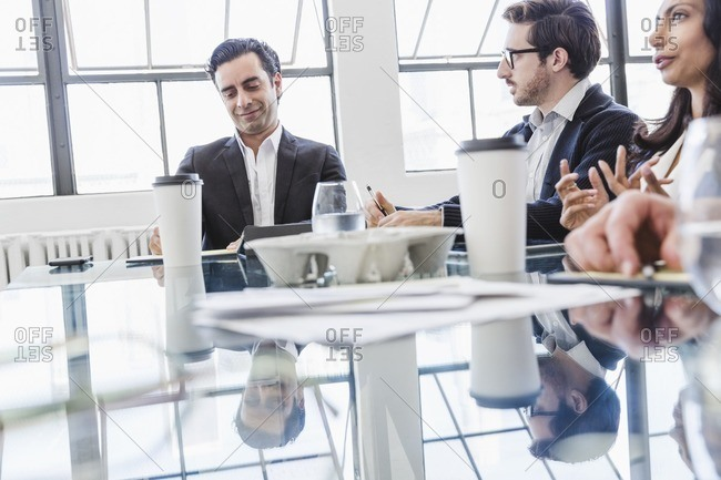 A group of business people meeting around an office table