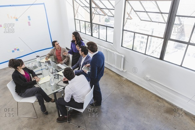 Overhead view of a group of people talking around an office table