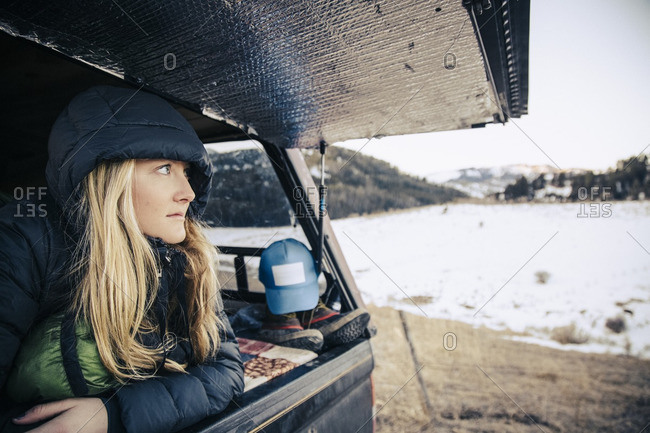Woman looking out from the rear hatch of a pick up truck camper