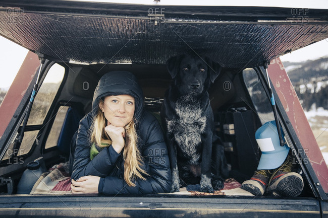 A woman and her dog looking out from the rear hatch of a pick up truck camper