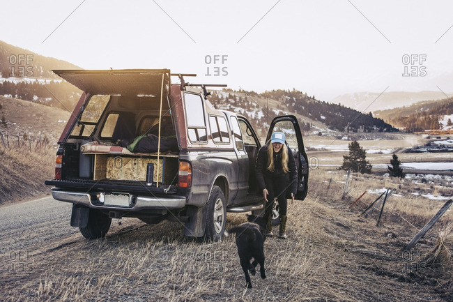 A woman and her dog parked along a rural road on a winter afternoon