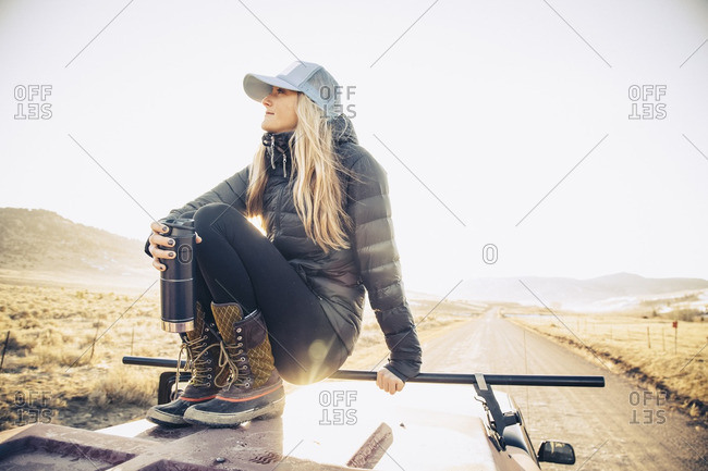 A woman sitting on the roof of her pick up truck with a canteen enjoying the view