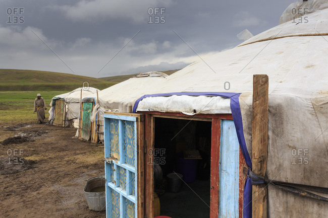 Gers at a Summer nomad camp under dark skies with nomadic man wearing deel, Khujirt, Uvurkhangai (Ovorkhangai), Central Mongolia, Central Asia, Asia