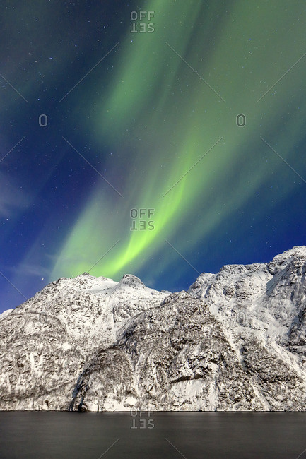 Northern Lights (aurora borealis) illuminate the snowy peaks and the blue sky during a starry night, Budalen, Svolvaer, Lofoten Islands, Arctic, Norway, Scandinavia, Europe