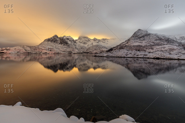 The light of the moon and snowy peaks reflected in the cold sea lit the night at Svolvaer, Lofoten Islands, Arctic, Norway, Scandinavia, Europe