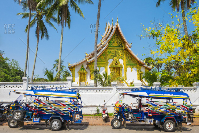 Louangphabang, Laos - May 14, 2015: Colorful tuk-tuks in front of Haw Pha Bang temple on the grounds of the Royal Palace Museum in Luang Prabang, Louangphabang Province, Laos, Indochina, Southeast Asia, Asia