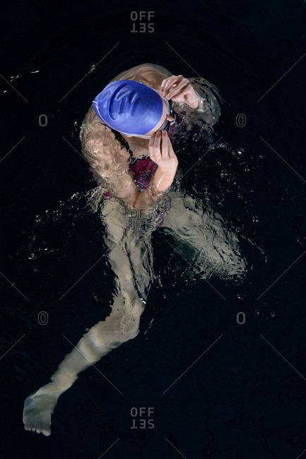Teenage girl adjusting goggles in swimming pool