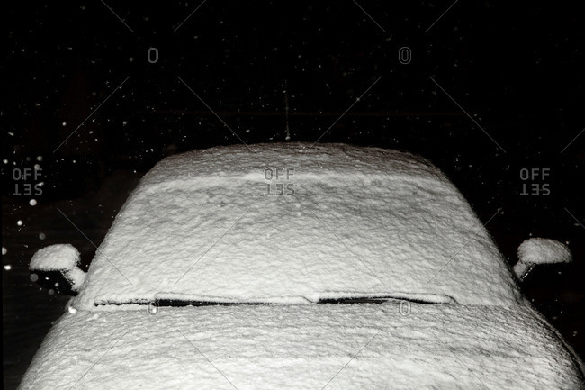 Windshield of snow-covered car in driveway