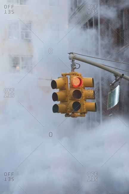 Traffic light on steamy city street