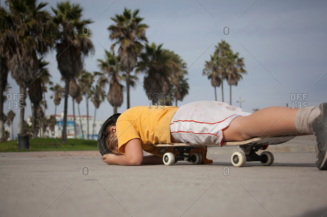 Boy laying on skateboard in park