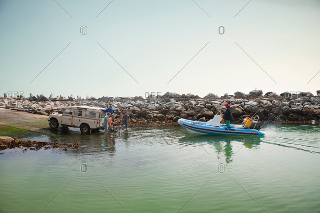 Western Cape, South Africa - April 14, 2013: Small group of men landing dinghy in harbor