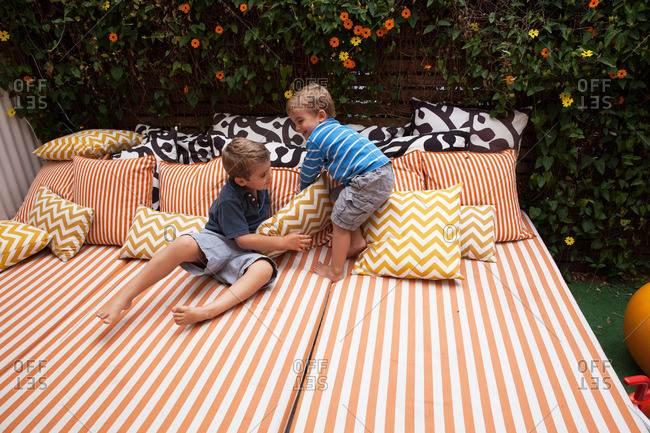 Two boys playing on outdoor  furniture with cushions