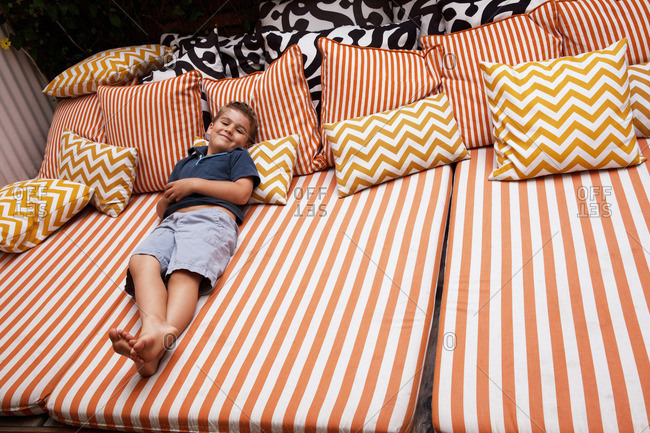 Boy relaxing on striped outdoor  furniture with cushions
