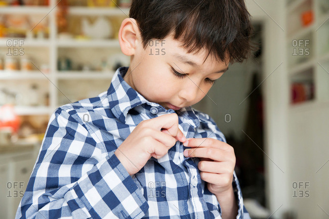 Close up portrait of young boy fastening shirt buttons