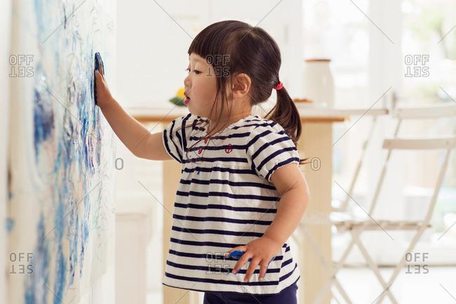 Female toddler making handprint painting