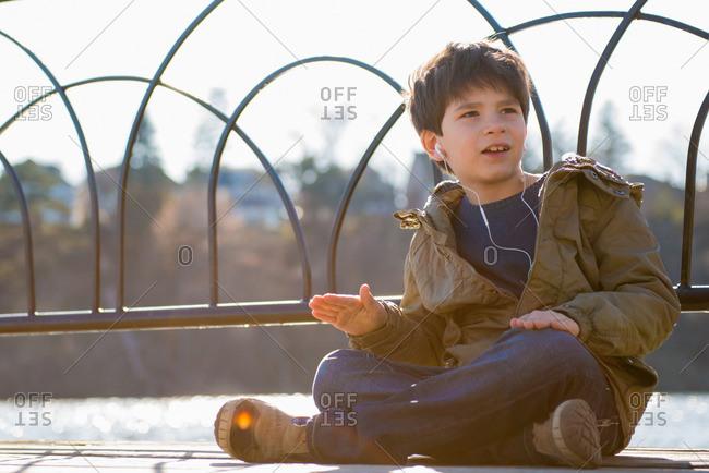 Boy sitting cross legged wearing earphones
