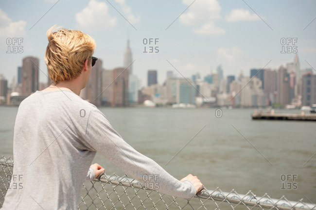 Young man looking at city skyline, Brooklyn, New York City, USA