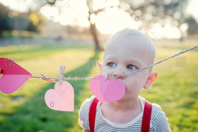 Young boy looking over heart shapes on washing line