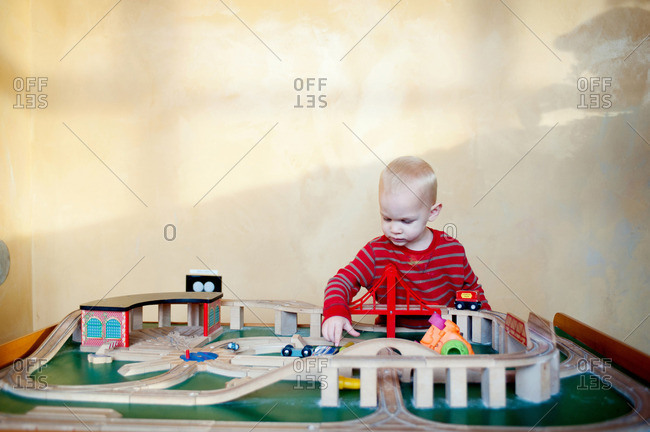 Young boy playing with toy train set