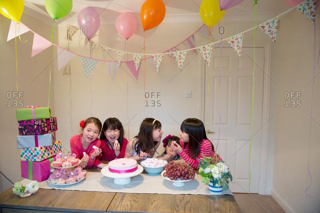 Girls sharing birthday cake at party