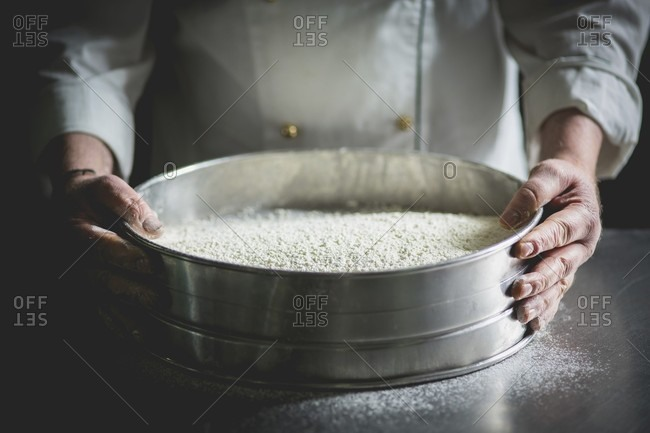 A confectioner with a large sieve of icing sugar