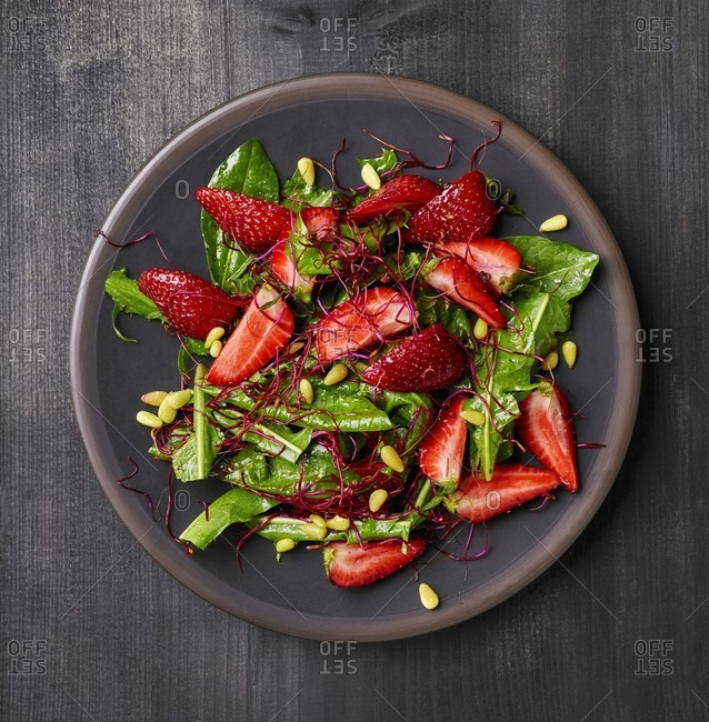 Dandelion salad with strawberries, beetroot sprouts and pine nuts