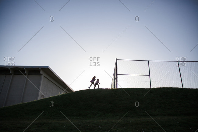 Two girls silhouetted at top of hill by fenced schoolyard