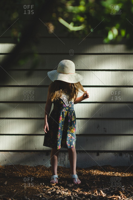 Young girl in dress and straw hat in shade