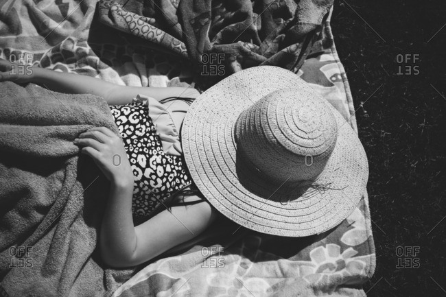 Sunbathing girl with hat over her face