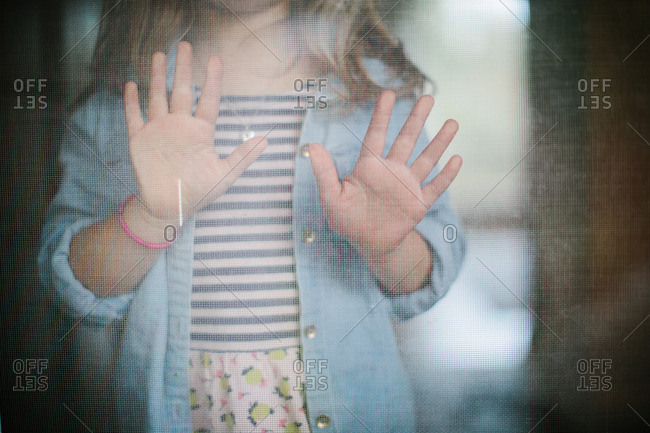Young girl with her hands pressed against screen