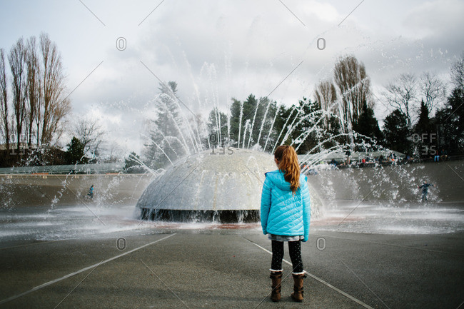 Girl observing a public fountain in city park