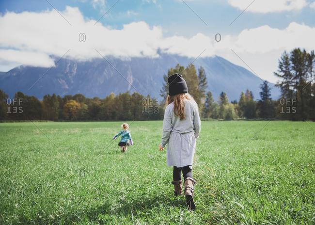 Back view of two young girls walking in field below mountain