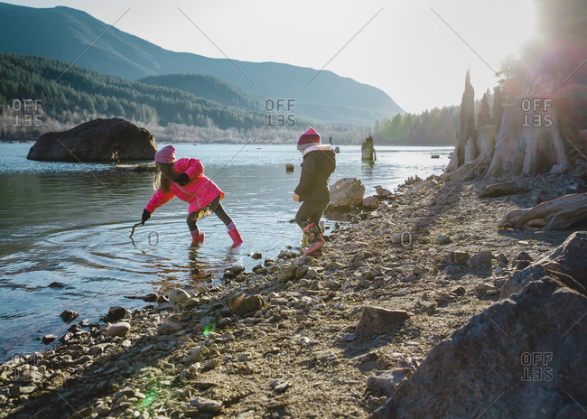 Two girls in winter coats and hats play at edge of lake