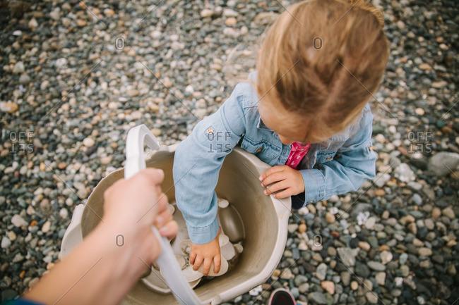 Parent holding pail as daughter places rocks inside
