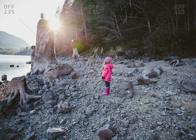 Young girl in pink coat explores shore of lake in mountains