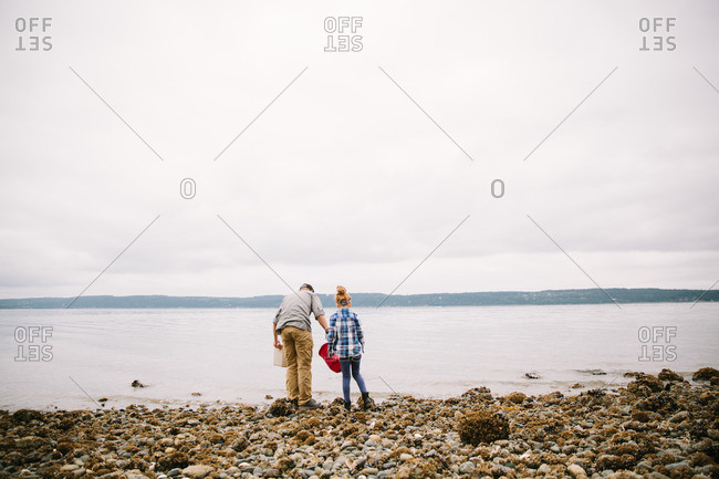 Father and daughter exploring water's edge on rocky beach