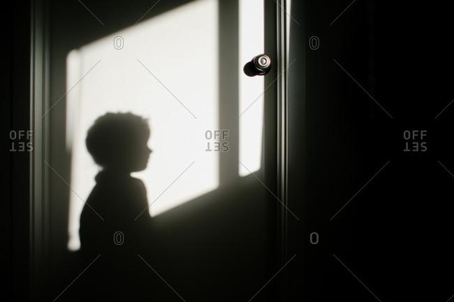 Child's profile in shadow on door