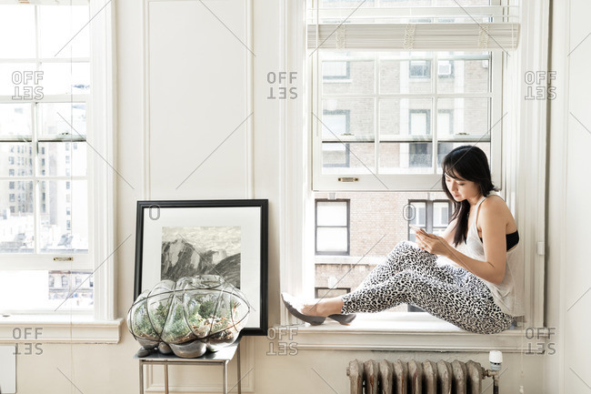 Side view of woman using smart phone while sitting on window sill at home