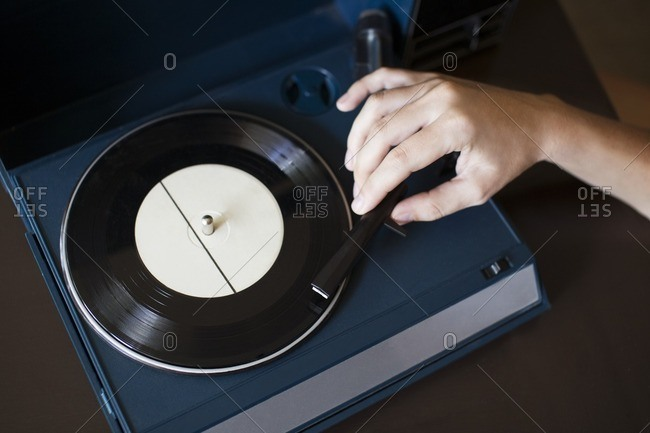 Cropped image of woman playing record player on table