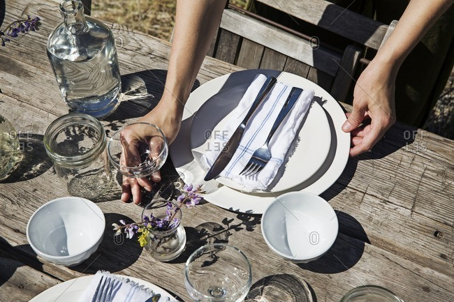 Cropped image of hands arranging crockery on table