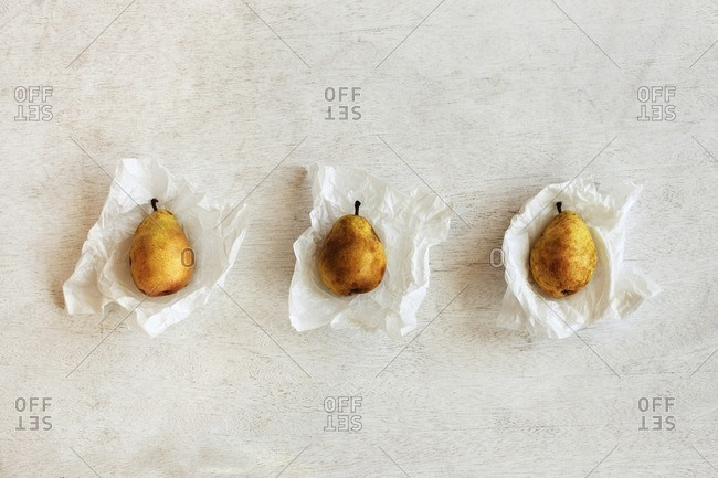 Overhead view of pears in wax papers arranged on wooden table