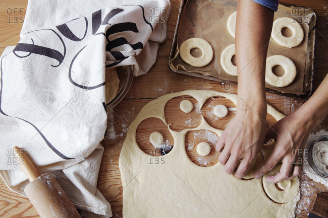 Overhead view of woman preparing donuts on wooden table