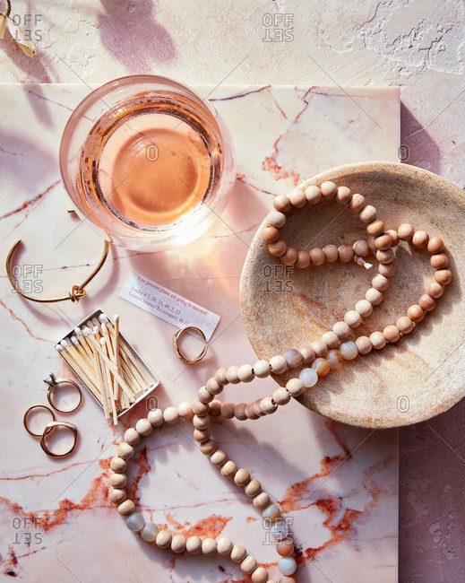 Jewelry, matches, and a glass of wine on a marble slab