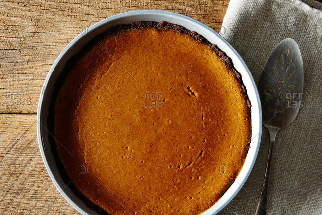 A pumpkin pie on wood background