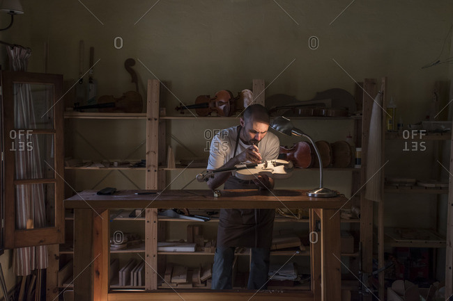 Luthier examining the sound post of an unvarnished violin in his workshop