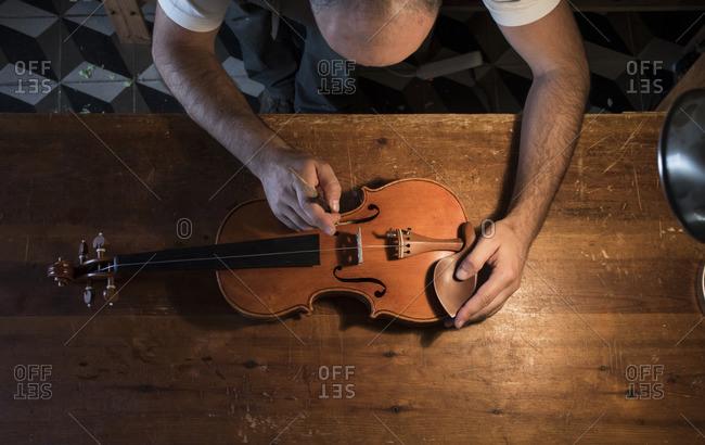 Luthier adjusting the sound post of a violin in his workshop