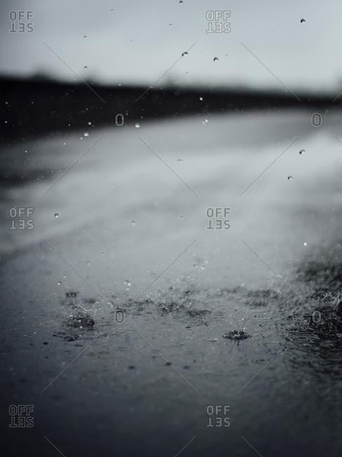 Raindrops splashing on tarmac