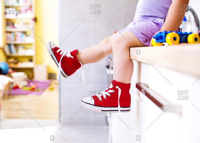 Little girl sitting in kitchen with read canvas shoes