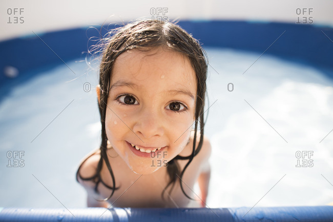 Portrait of smiling little girl in a paddling pool